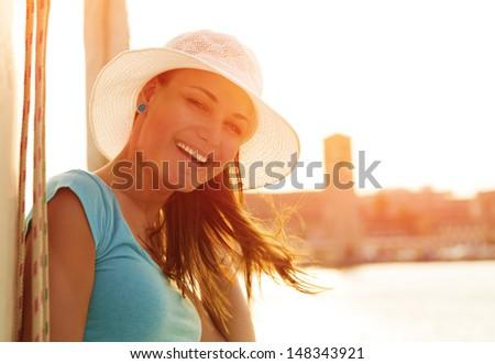 Closeup portrait of cute smiling woman on orange sunset background, wearing white stylish hat, glamorous lifestyle, wonderful trip on the yacht - stock photo