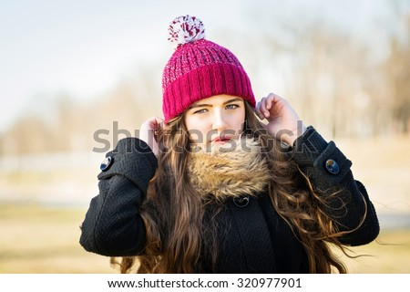 Closeup portrait of cute teenage girl outdoors in cold weather, autumn or winter, posing wearing black coat and red crocheted beanie hat. Retouched, horizontal, no filter. - stock photo