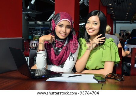 Closeup portrait of cute two young business woman with lovely smile