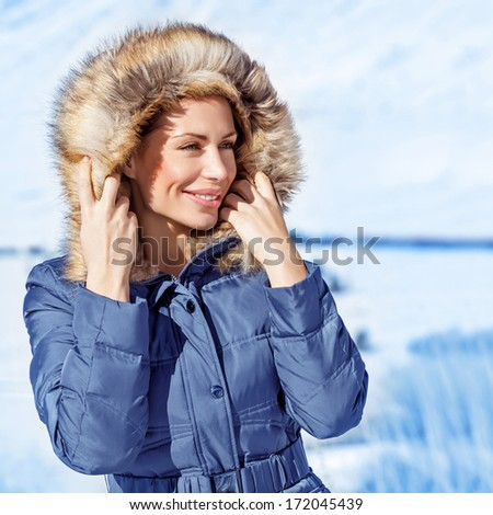 Closeup portrait of cute woman wearing warm coat with hood with fur, having fun in winter park, wintertime fashionable style, vacation concept - stock photo