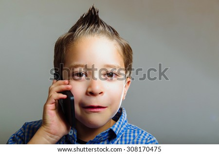 Closeup portrait of cute young boy talking using mobile phone - stock photo