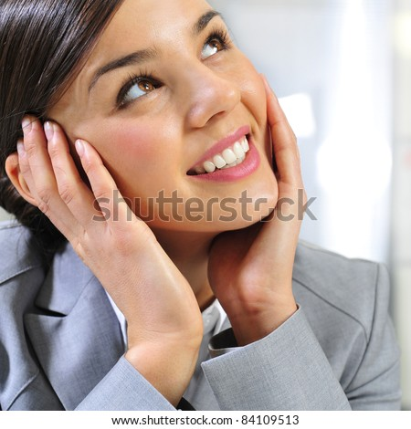 Closeup portrait of cute young business woman smiling and daydreaming - stock photo