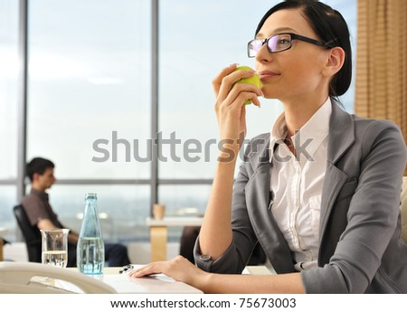 Closeup portrait of cute young business woman smiling at her workplace in an office environment. Eating green apple