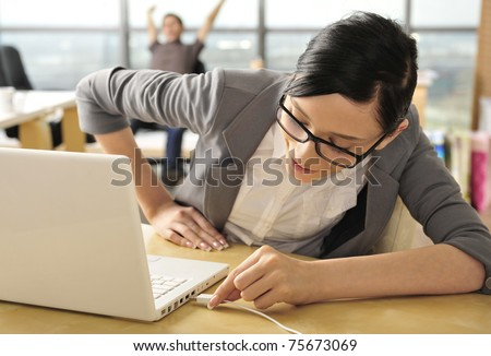 Closeup portrait of cute young business woman smiling at her workplace in an office environment. Connecting usb device to port on laptop - stock photo