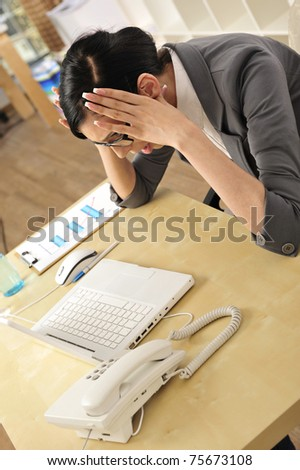 Closeup portrait of cute young business woman smiling at her workplace in an office environment. Hands on a head - tired - stock photo