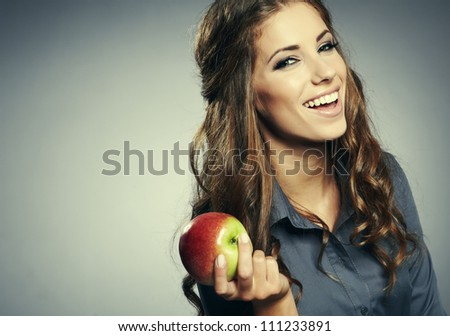 Closeup portrait of cute young business woman smiling at studio. Eating  apple - stock photo
