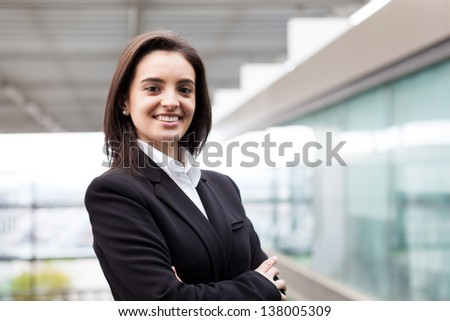 Closeup portrait of cute young business woman smiling at the office