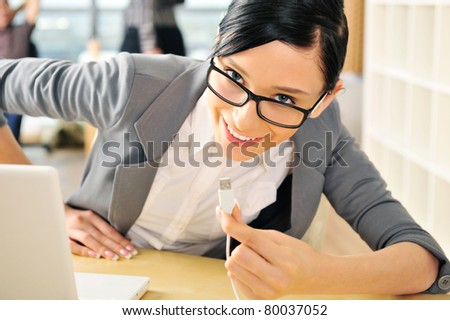 Closeup portrait of cute young business woman smiling. Sitting at her workplace using laptop and inserting usb - stock photo