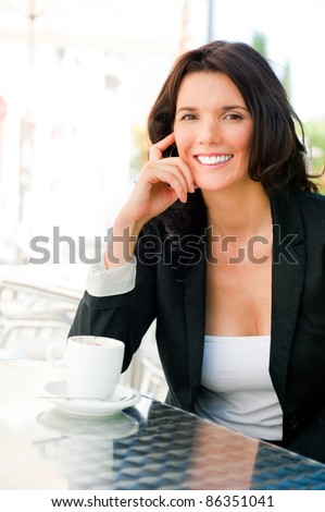 Closeup portrait of cute young business woman smiling while drinking her coffee at outdoor cafe