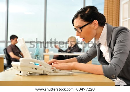 Closeup portrait of cute young business woman using laptop and looking at the screen at her workplace in an office environment. Her colleagues at the back. She is confused - stock photo