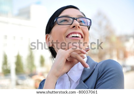 Closeup portrait of cute young business woman wearing glasses smiling. Outdoor against office building and beautiful view