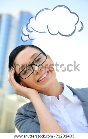 Closeup portrait of cute young business woman wearing glasses smiling. Outdoor against office building and beautiful view. Blank cloud balloon overhead - stock photo
