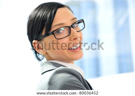 Closeup portrait of cute young business woman wearing glasses smiling. Sitting against big french window - stock photo