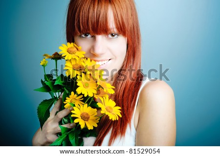 Closeup portrait of cute young girl with yellow flowers smiling - stock photo