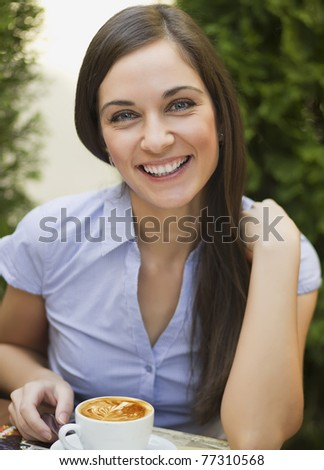 Closeup portrait of cute young woman sitting and smiling in the cafe with a cup of coffee