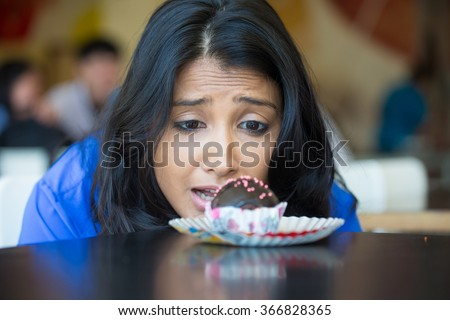 Closeup portrait of desperate woman in blue shirt craving fudge with pink sprinkles dessert, eager to eat, isolated indoors background - stock photo