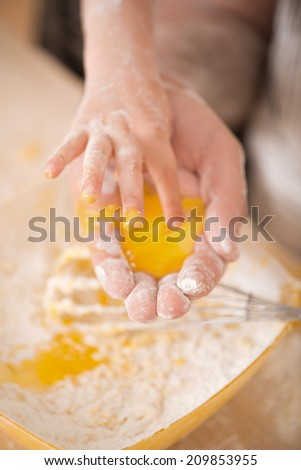 Closeup portrait of egg yolk in cooks hand, child touching it with finger on the background of dirty kitchen table covered with flour - stock photo