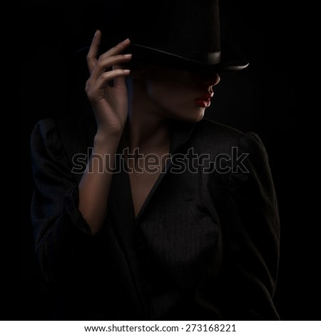 closeup portrait of elegant blond retro woman in hat over dark background - stock photo