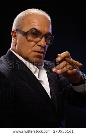 Closeup portrait of elegant mature man smoking cigar, looking at camera. - stock photo