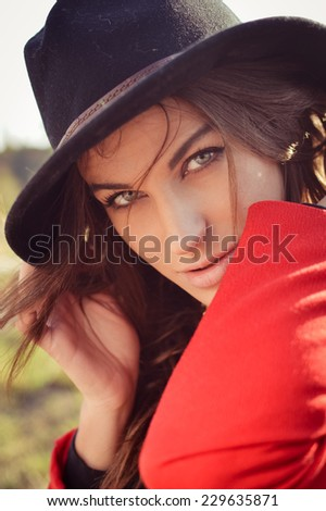 closeup portrait of elegant pretty young lady in red jacket having fun joyfully looking at camera & sensually smiling on autumn background - stock photo