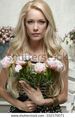 Closeup portrait of fashion model posing with bunch of peony