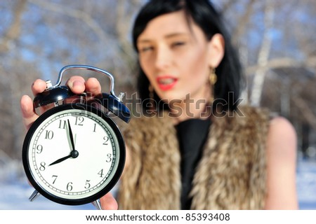 Closeup portrait of fashionable woman wearing fur clothes holding alarm on foreground and reminding about time to buy christmas gifts - stock photo