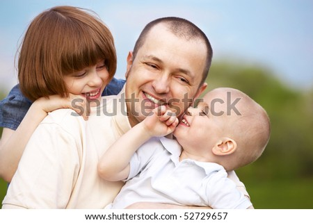closeup portrait of father and two children outdoor - stock photo
