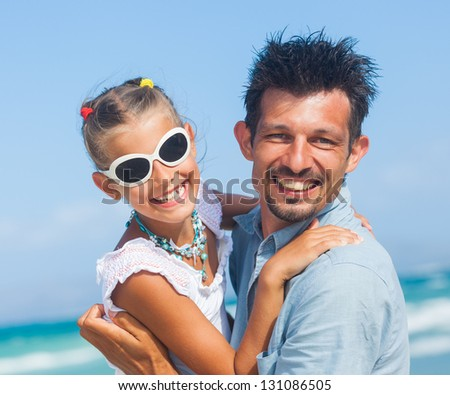 Closeup portrait of father with daughter having fun on tropical beach - stock photo