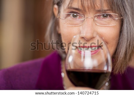 Closeup portrait of female customer drinking red wine in restaurant - stock photo