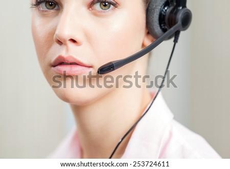 Closeup portrait of female customer service representative wearing headset in office - stock photo
