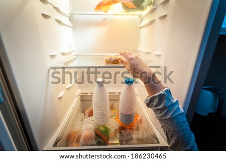 Closeup portrait of female hand taking donut from fridge