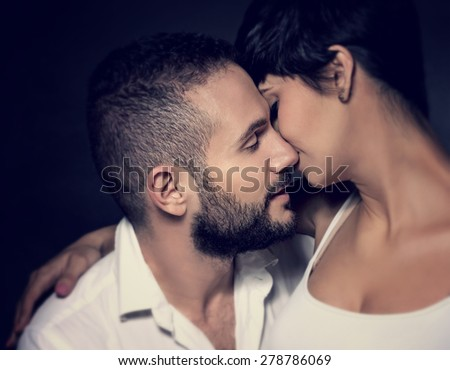 Closeup portrait of gentle loving couple kissing isolated on black background, enjoying romantic relationship, affection and tenderness concept - stock photo