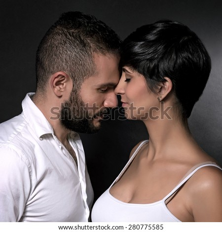 Closeup portrait of gentle loving couple over black background, enjoying each other, romantic relationship, affection and tenderness concept - stock photo