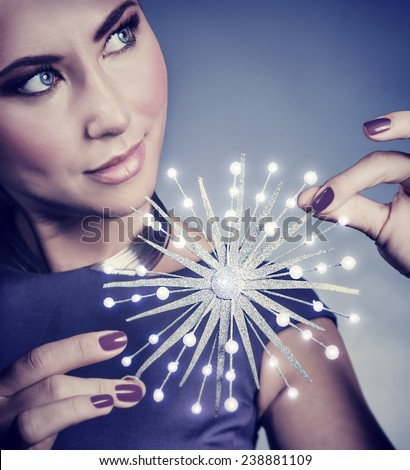 Closeup portrait of gorgeous female with beautiful festive makeup holding in hands glowing snowflake, luxury Christmas accessories - stock photo