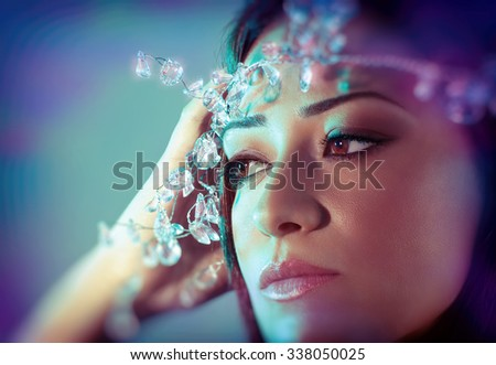 Closeup portrait of gorgeous woman with perfect makeup wearing luxury diamonds wreath over blue background, stylish look for Christmas party - stock photo