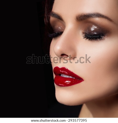 Closeup portrait of gorgeous young woman with glossy eyeshadows and red lips. Square composition. Copy space.