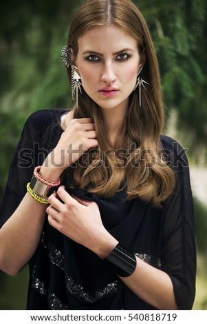 Closeup portrait of gorgeous young woman with unusual earrings