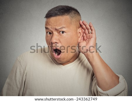 Closeup portrait of guy listening in on a conversation and seeming shocked by what he hears isolated on grey background with copy space