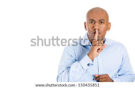 "Closeup portrait of handsome bald man placing finger on lips as if to say, ""shhhhh"", ""be quiet"", ""silence"" , isolated on white background with copy space - stock photo"
