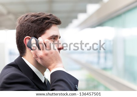 Closeup portrait of handsome business man using cell phone at the office - stock photo