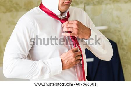 Closeup portrait of  handsome businessman in suit putting on necktie indoors - stock photo