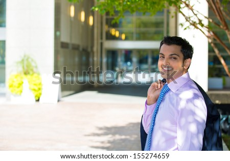 Closeup portrait of handsome businessman in suit relaxing outside of his office during a lunch break on a sunny day, isolated on a city urban background. Corporate success - stock photo