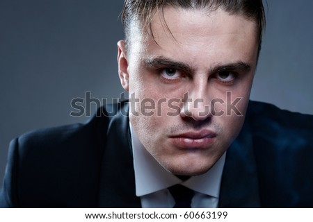 Closeup portrait of handsome displeased young man in suit - stock photo