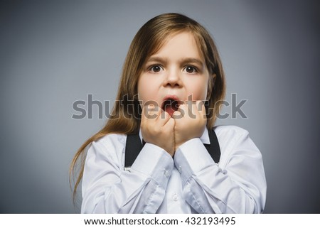 Closeup Portrait of handsome girl with astonished expression while standing against grey background - stock photo