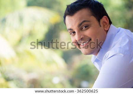 Closeup portrait of handsome happy young man in blue shirt standing outside on his balcony, isolated outdoors outside background with green trees