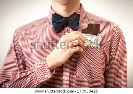 Closeup portrait of handsome hipster man in shirt and bow tie taking chocolate out of breast-pocket - stock photo