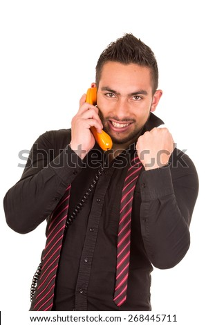 closeup portrait of handsome hispanic man talking on corded retro phone with fist up receiving good news isolated on white - stock photo