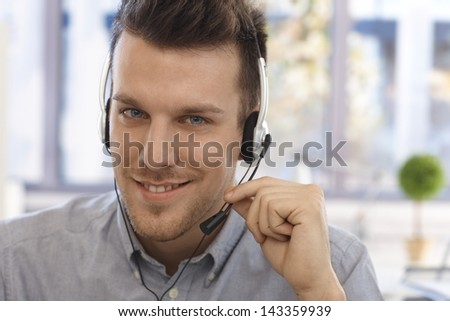 Closeup portrait of handsome male dispatcher working, looking at camera. - stock photo