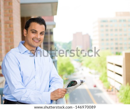 Closeup portrait of handsome man reading newspaper on his outside balcony isolated on a city background with trees, buildings and cars - stock photo