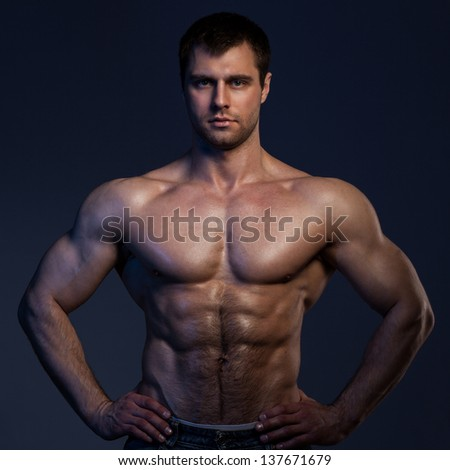 Closeup portrait of handsome muscular guy on dark background - stock photo